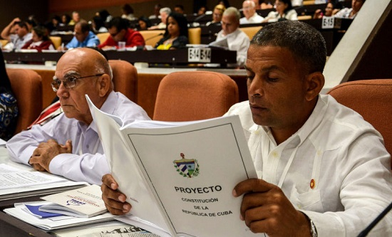 Delegates to Cuba's National Assembly review the proposed constitutional changes