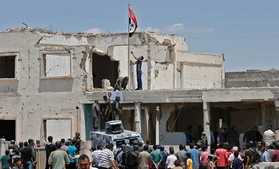 Syrian security forces raising the government flag