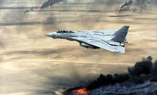 A US Navy jet flies over burning Kuwaiti oil fields during Operation Desert Storm